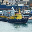 Tugboat at military ship at harbor - Stockfoto