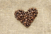Heart with coffee beans on burlap — Stock Photo