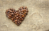 Coffee beans in the shape of a heart on the burlap — Stock Photo