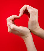 Hands as heart on red background — Stock Photo