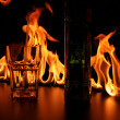 Royalty-Free Stock Photo: Fireshow on bar rack with glasses and bottle