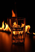 Fireshow on bar rack with glasses — Stock Photo