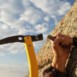 Hands rock-climber hammering in hook in rock — Stock Photo