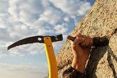 Hands rock-climber hammering in hook in rock — Stock Photo
