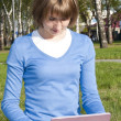She is working on a laptop in the park — Stock Photo