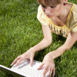 Young woman with laptop sitting on green grass — Stock Photo #5888675