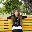 Young girl sits in park on bench — Stockfoto #5906054