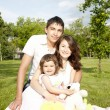 Stock Photo: Portrait of family embracing on grass in park