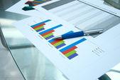 Papeles, tablas de crecimiento, una mesa — Foto de Stock