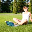 Stock Photo: Young girl sitting in the park with your laptop