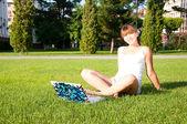 Giovane ragazza seduta nel parco con il tuo portatile — Foto Stock