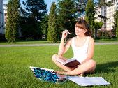 Chica joven estudiando en el parque — Foto de Stock