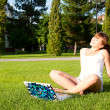 Young girl sitting in the park with your laptop — ストック写真