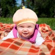 Portrait of the baby, on coverlet in the park — Stock Photo