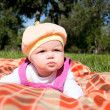 Stock Photo: Portrait of baby, on coverlet in park