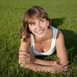 Beautiful young woman smiling on grass field — ストック写真