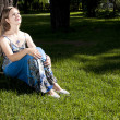 Beautiful womsitting under tree in park — Foto de stock #6097147