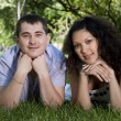 Couple lays together on a grass — Stock Photo