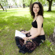 Stock Photo: Beautiful pregnant woman read book in the park