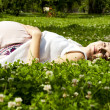 Foto Stock: Beautiful pregnant womrelaxing on grass