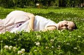 красивая беременная женщина, расслабляющий на траве — Стоковое фото