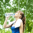 Stock Photo: Young woman drinking water after exercise