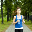 Young woman jogging in the park in summer — Stok fotoğraf