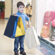 Little boy with the packages in the shop — Stok fotoğraf
