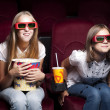 Two beautiful girls watching a movie at the cinema — Stock Photo