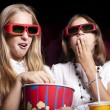 Two beautiful girls watching a movie at the cinema — ストック写真