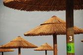 Straw parasols on beach — Stock Photo