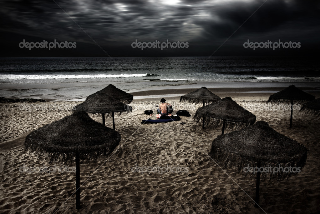 Night scene in a beach with a man sitting in the sand and playing his guitar — Stock Photo #5873829