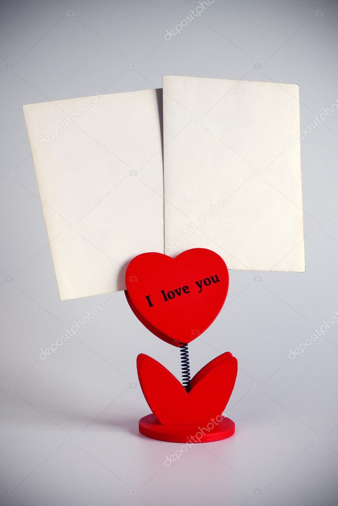 Heart-shaped photo holder saying I Love You holding two photos — Stock Photo #5874021