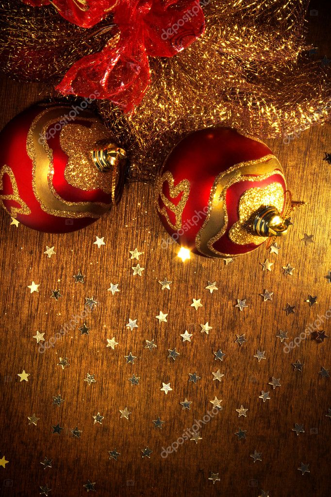 Two red and golden christmas balls and shining little stars over wooden surface — Stock Photo #5874556