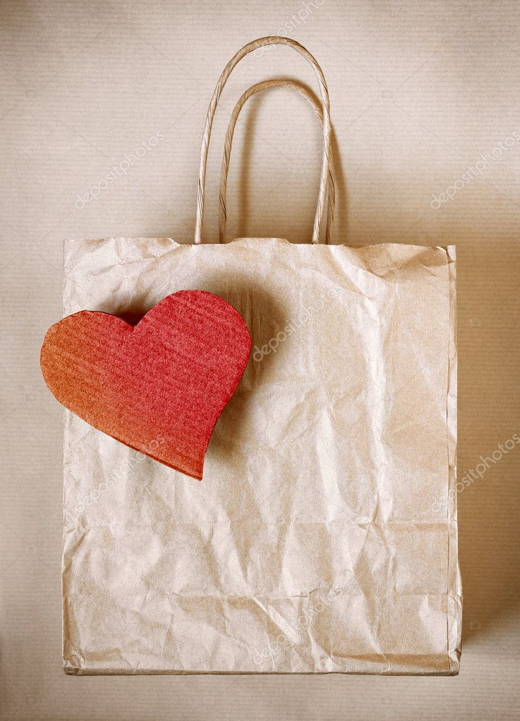 Worn paper bag with red cardboard heart over wrapping paper — Stock Photo #5874589