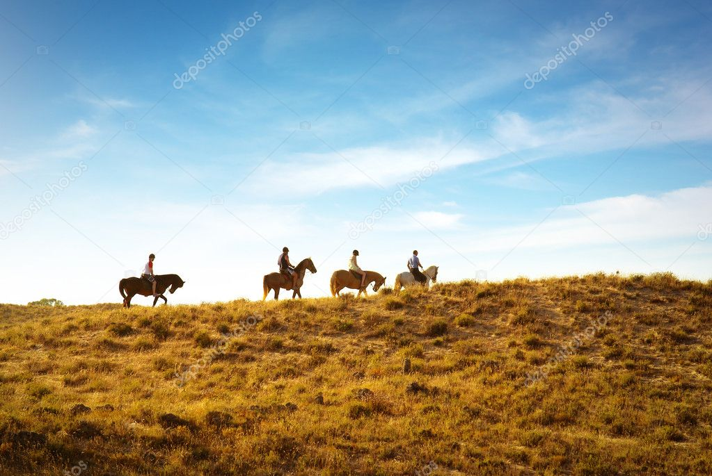 Horseback riding in the dunes near a beach at sunset  Stock Photo #5875039