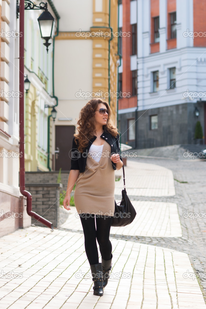 Fashionable girl walking down the street stock image