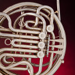 Stock Photo: Silver French Horn Isolated on Red