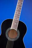 Black Acoustic Guitar On Blue — Foto Stock