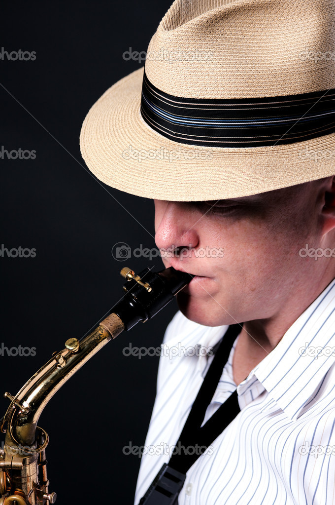 A professional jazz saxophone player isolated against black background in the vertical format.  Stock Photo #6256356