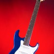 Blue Guitar Isolated Against Red — Stock Photo