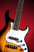 Sunburst Bass Guitar Isolated on Red — Stock Photo