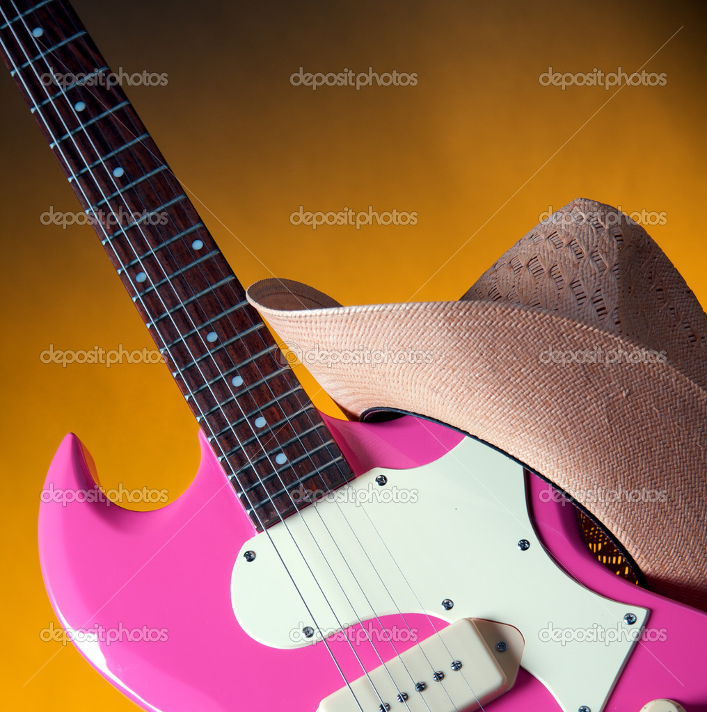 An electric pink guitar with a girl's or ladies western hat isolated against a gold or yellow background in the square format.  Stock Photo #6614982