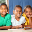 Three happy school girls reading a book in class - Stock Photo