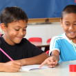 Two schoolboys helping each other learn in class during lessons — Stock Photo #5867074