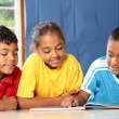 Three primary school friends reading and learning — Stock Photo