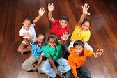 Six school children on classroom floor — Stock Photo