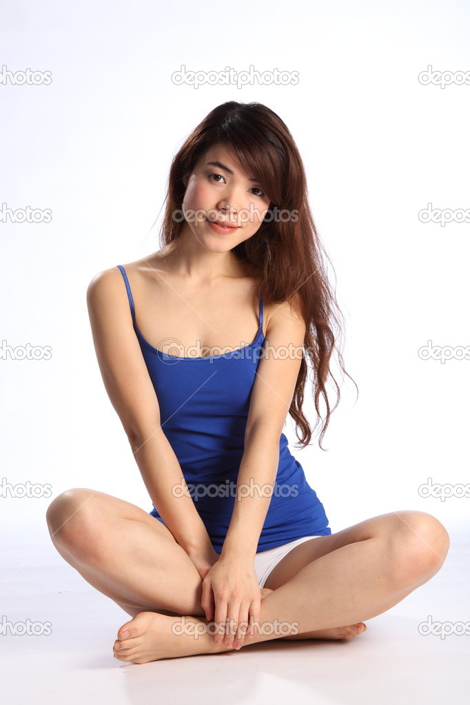 Beautiful young oriental girl, sitting on floor, cross legged. Girl wearing vest and underwear, showing off a healthy body. — Stock Photo #5867415
