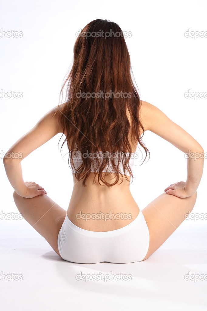 Beautiful young oriental girl, sitting on floor with back to camera, wearing white underwear, showing off a healthy body. — Stock Photo #5867435