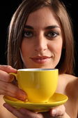 Woman with yellow tea cup and saucer — Stock Photo
